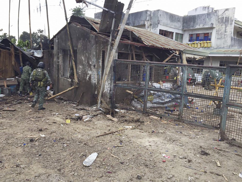 In this Friday, June 28, 2019 photo, Philippine troops examine the scene of the suicide attack carried out by Muslim militants at a military camp in I