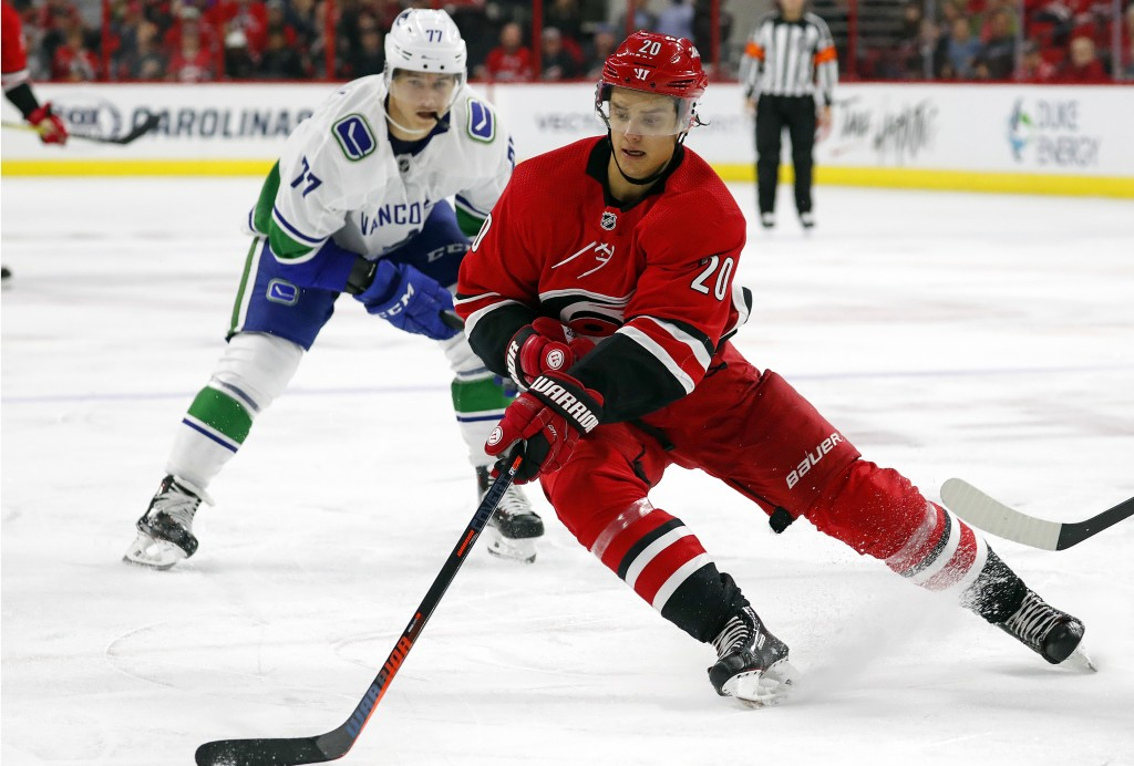 FILE - In this Oct. 9, 2018, file photo, Carolina Hurricanes' Sebastian Aho (20) gathers in the puck in front of Vancouver Canucks' Nikolay Goldobin (