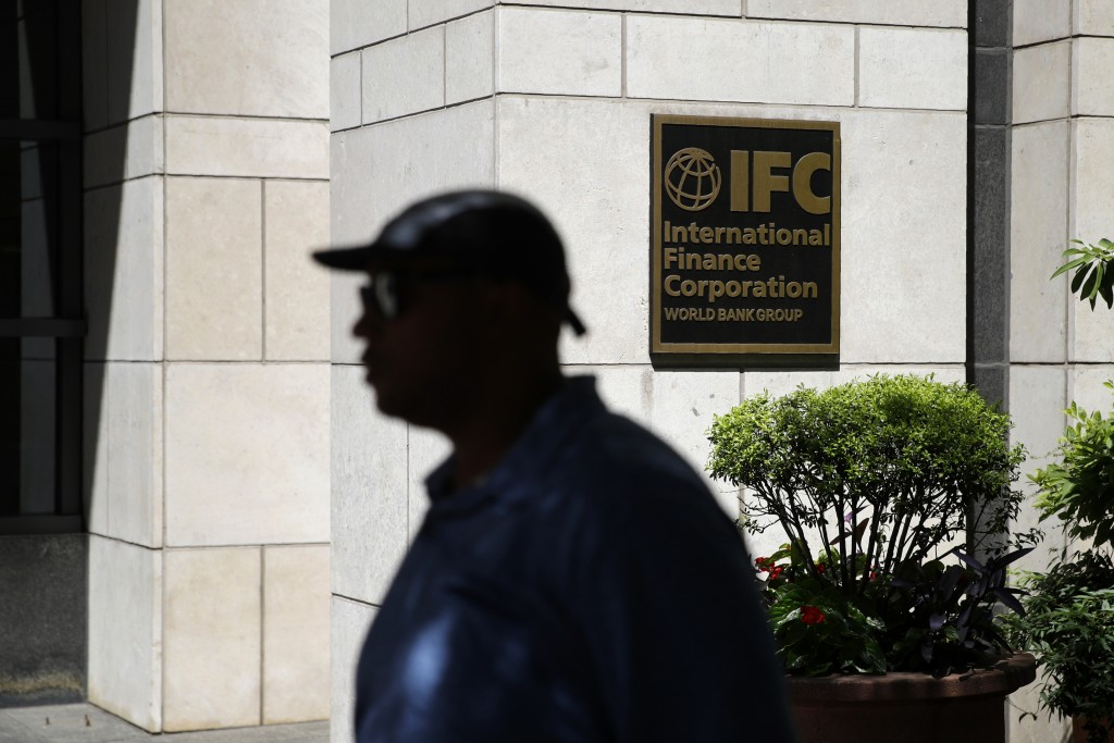 In this June 12, 2019, photo, a man walks past an entrance to the International Finance Corporation, a unit of the World Bank Group, in Washington. Th...