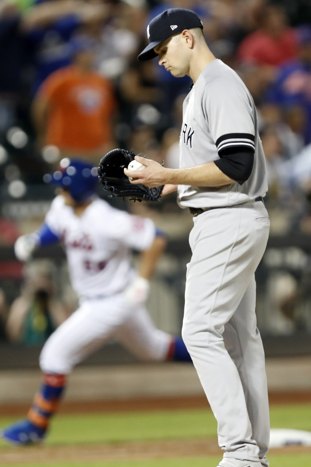 New York Mets' J.D. Davis, left, runs the bases past New York Yankees' starting pitcher James Paxton, who looks at the ball after allowing a solo home