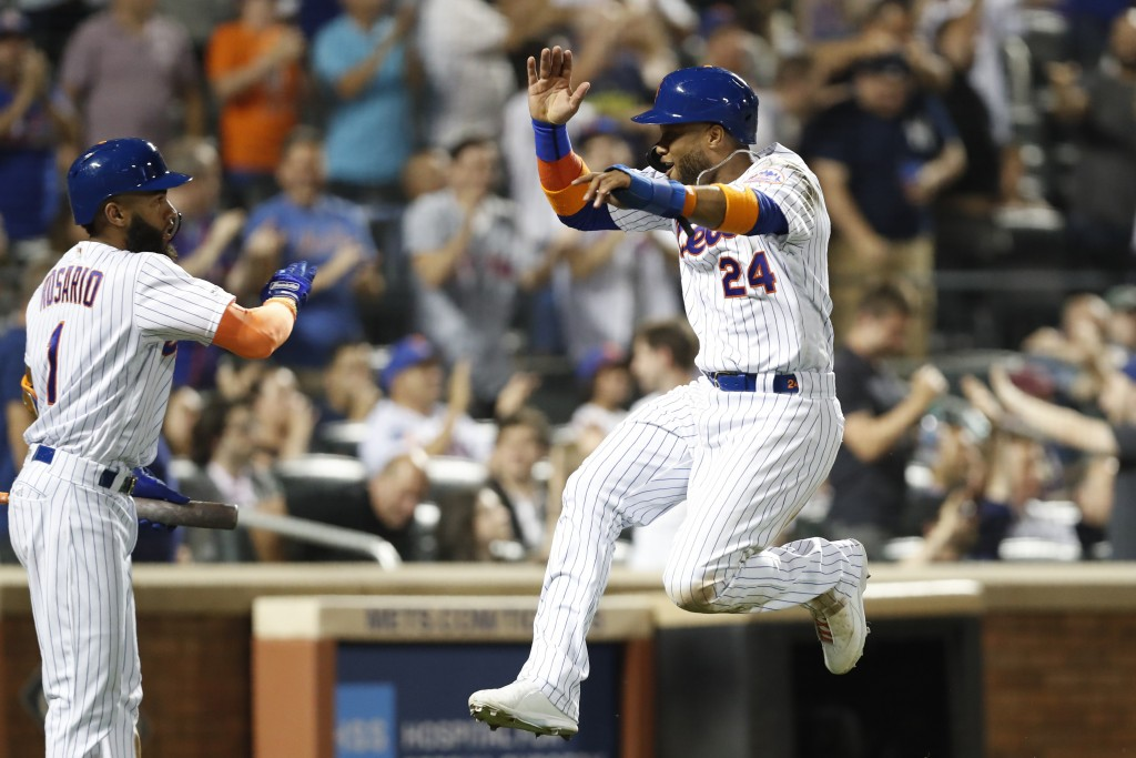 New York Mets' on-deck batter Amed Rosario, left, congratulates Robinson Cano (24) as he scores on Michael Conforto's two-run double in the eighth inn...
