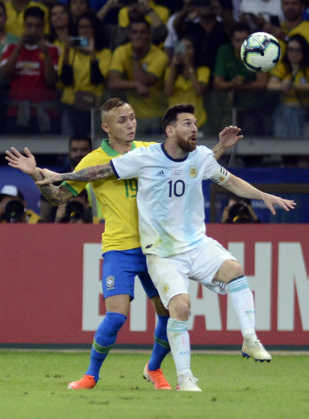 Brazil's Everton, left, fights for the ball with Argentina's Lionel Messi during a Copa America semifinal soccer match at Mineirao stadium in Belo Hor...