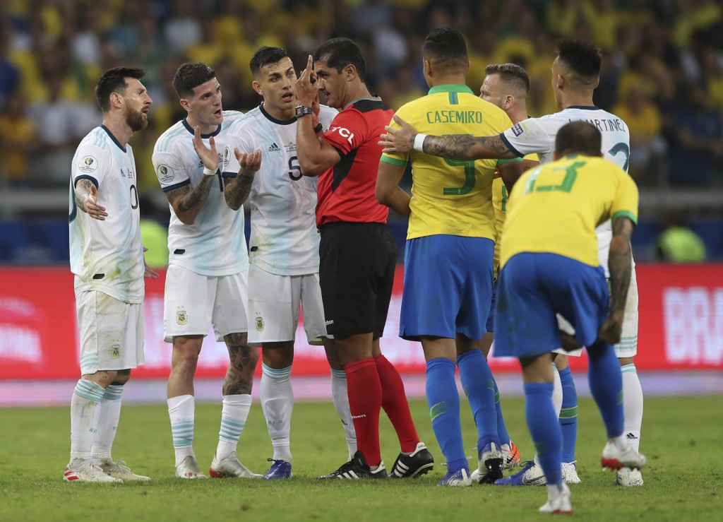 Argentina's Lionel Messi, left, and teammates complain with referee Roddy Zambrano after he was fouled during a Copa America semifinal soccer match at...