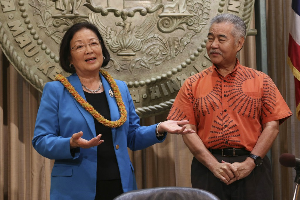 Hawaii Gov. David Ige, right, listens as U.S. Sen. Mazie Hirono speaks before Ige signs bills in Honolulu, Tuesday, July 2, 2019. Ige signed legislati...