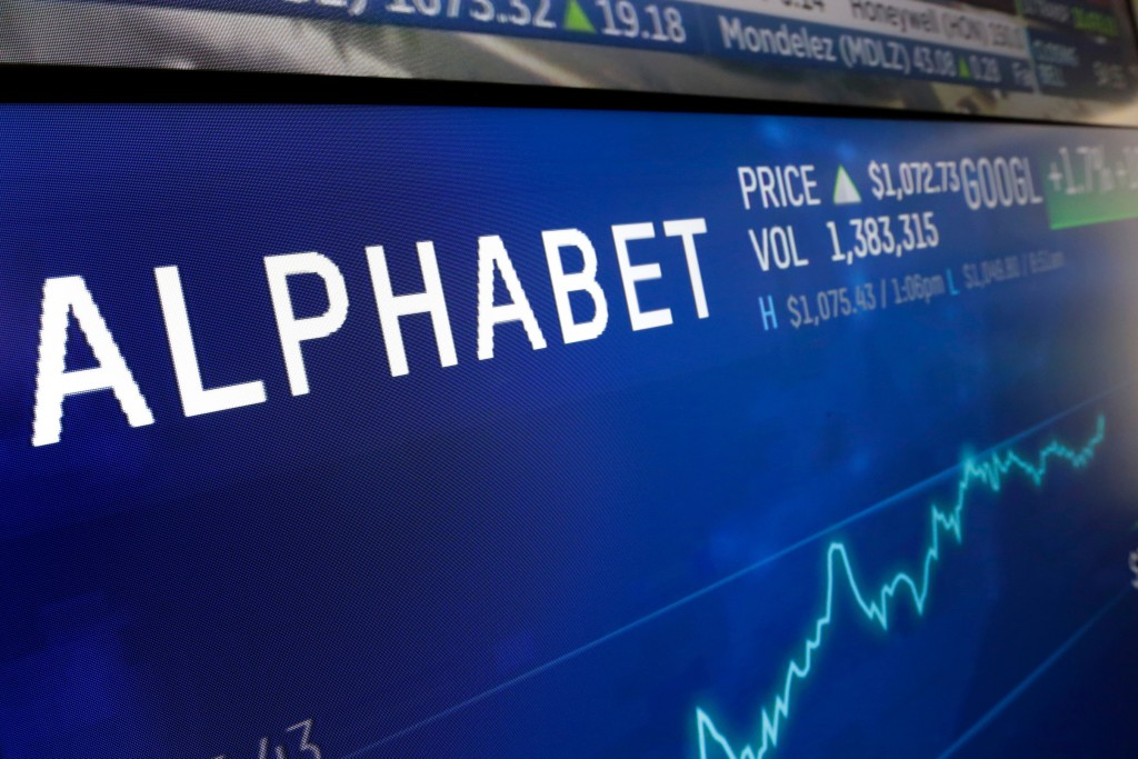 FILE- In this Feb. 14, 2018, file photo the logo for Alphabet appears on a screen at the Nasdaq MarketSite in New York.  Uncertainty over U.S. trade c...