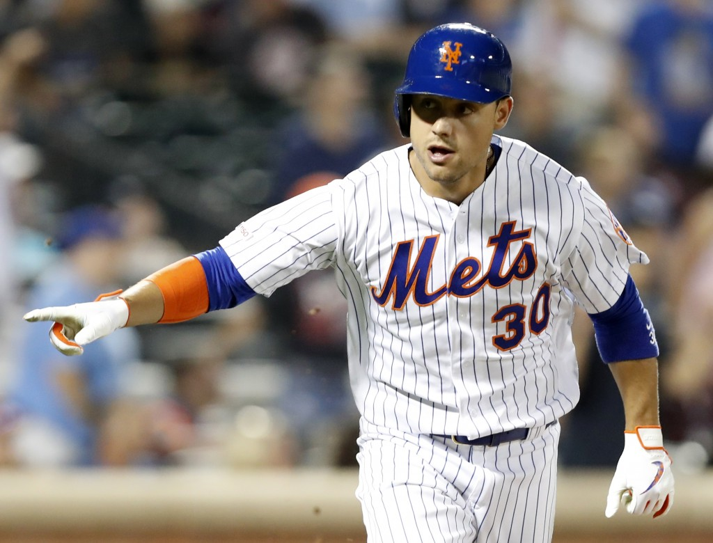 New York Mets' Michael Conforto gestures toward the dugout as he runs down the first base line after hitting a two-run double during the eighth inning...