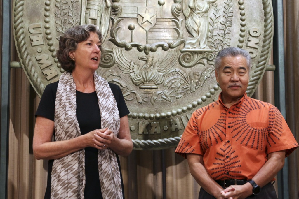 Hawaii Gov. David Ige, right, listens as Hawaii state Sen. Laura Thielen speaks before Ige signs bills in Honolulu, Tuesday, July 2, 2019. Ige signed ...