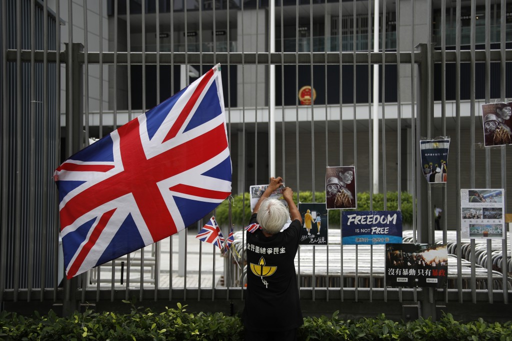A protester hangs posters near a British flag tied to the fence at the Central Government Office building in Hong Kong on Thursday, July 4, 2019. Hong