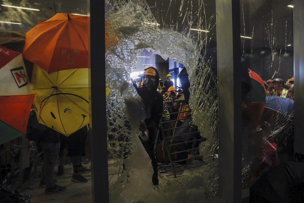 In this file photo taken Monday, July 1, 2019, a protester breaks the glass wall to enter the Legislative Council in Hong Kong, Protesters in Hong Kon