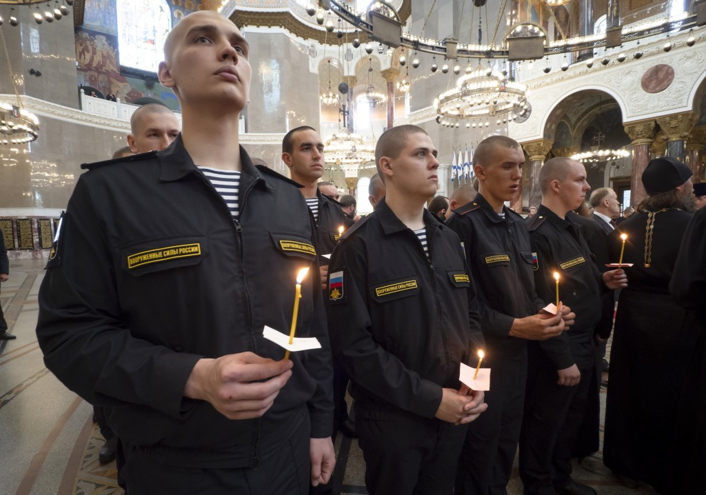 Navy sailors attend a religion service to commemorate the crew members that were killed on one of the Russian navy's deep-sea research submersibles at...