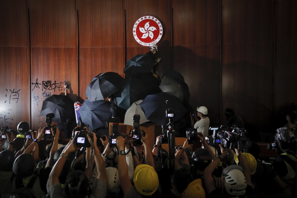 FILE - In this file photo taken Monday, July 1, 2019, journalists film a protester about to deface the Hong Kong emblem inside the meeting hall of the...