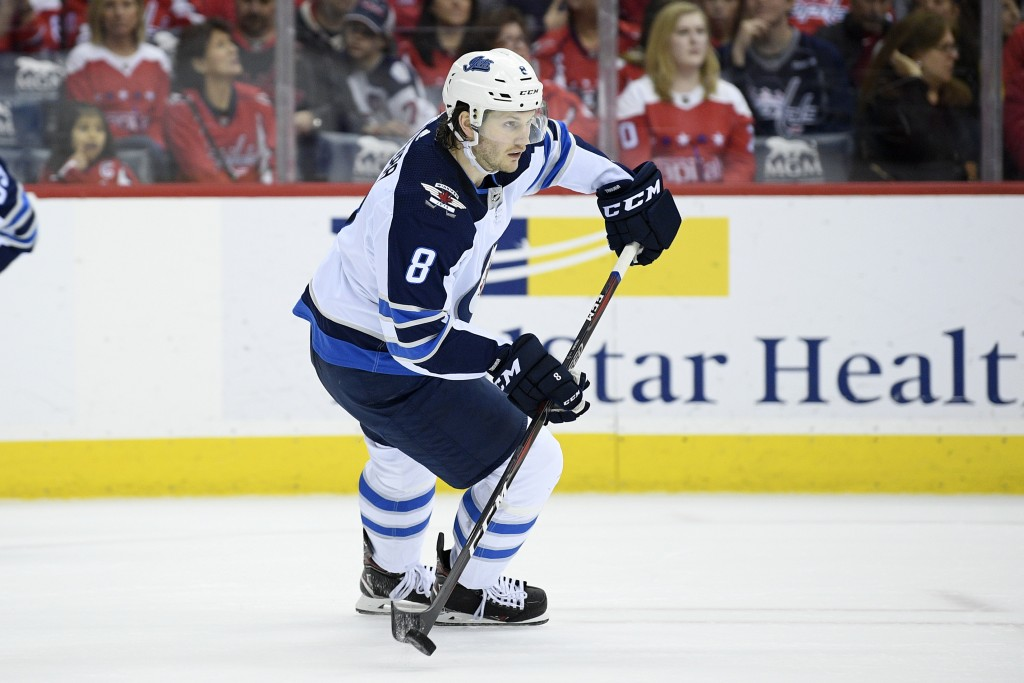 FILE - In this March 10, 2019, file photo, Winnipeg Jets defenseman Jacob Trouba (8) skates with the puck during the first period of an NHL hockey gam...