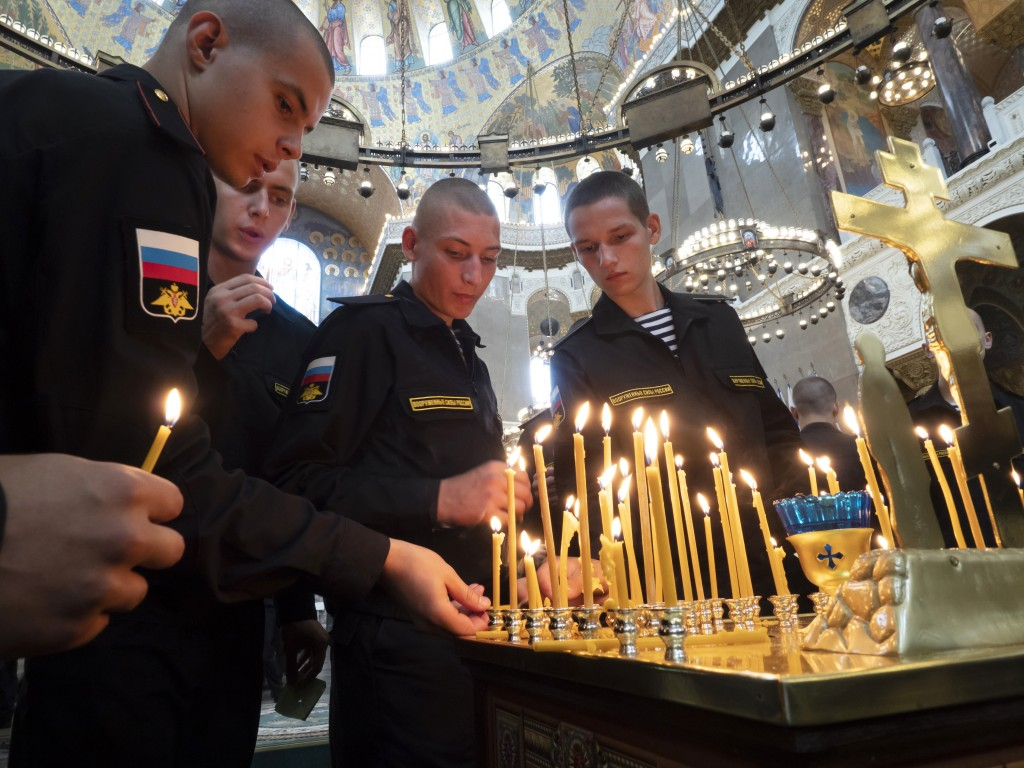 Navy sailors light candles during a religion service to commemorate the crew members that were killed on one of the Russian navy's deep-sea research s