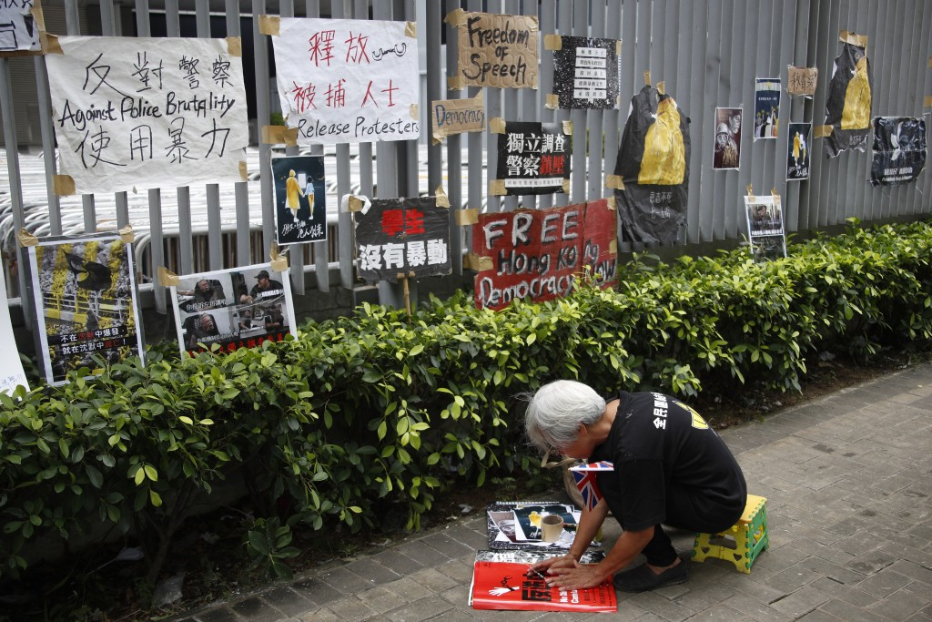 A protester prepares to hang posters against police brutality and calling for the release of arrester protesters outside the Central Government Office