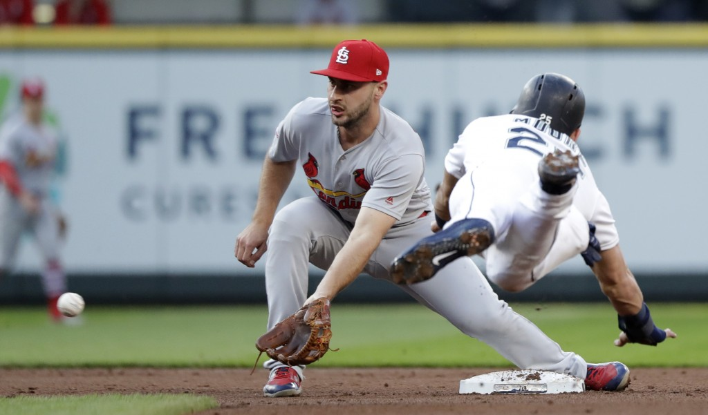 St. Louis Cardinals shortstop Paul DeJong, left, reaches for the ball before tagging out Seattle Mariners' Dylan Moore at second on a stolen-base atte