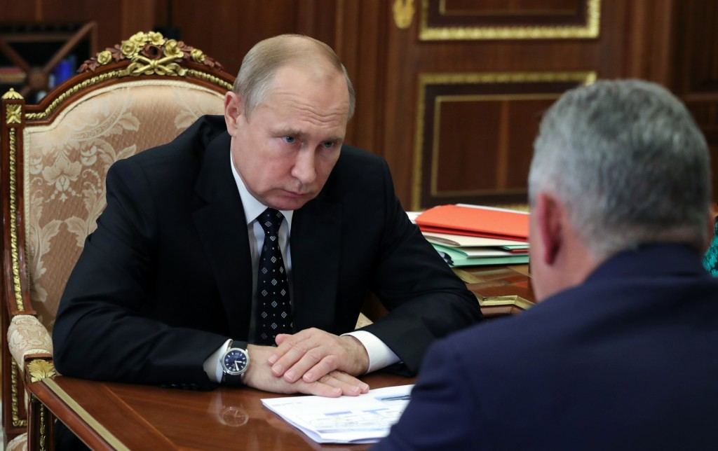 Russian President Vladimir Putin, left, listens to Russian Defense Minister Sergei Shoigu during their meeting in the Kremlin in Moscow, Russia, Thurs...