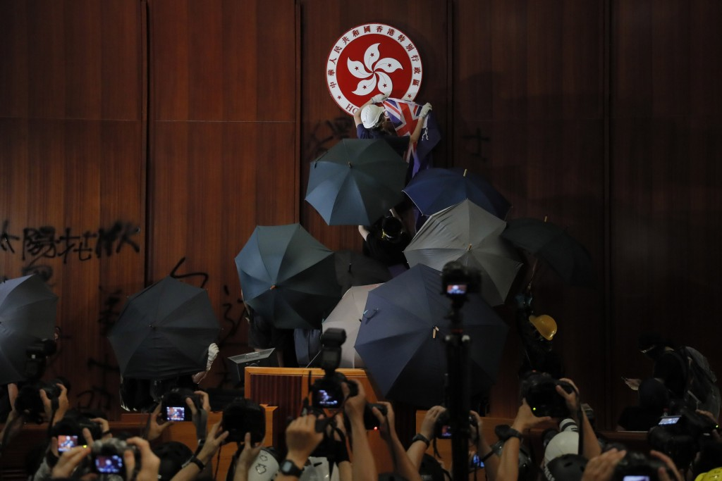 FILE - In this Monday, July 1, 2019, file photo, a protester covers the Hong Kong emblem with a Hong Kong colonial flag after they broke into the Legi...