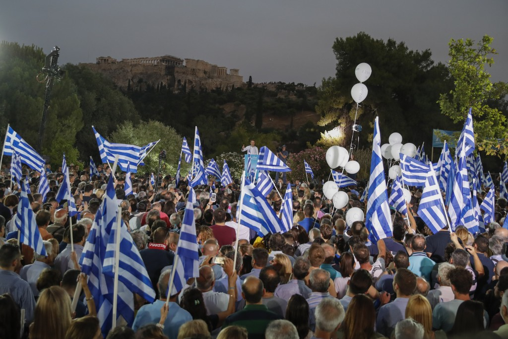 Supporter wave Greek flags as Greek opposition New Democracy party leader Kyriakos Mitsotakis, center, speaks during his main election campaign rally