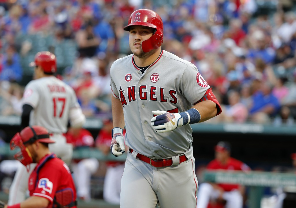 Los Angeles Angels' Mike Trout jogs to the dugout after hitting a solo home run off Texas Rangers' Lance Lynn during the first inning of a baseball ga...