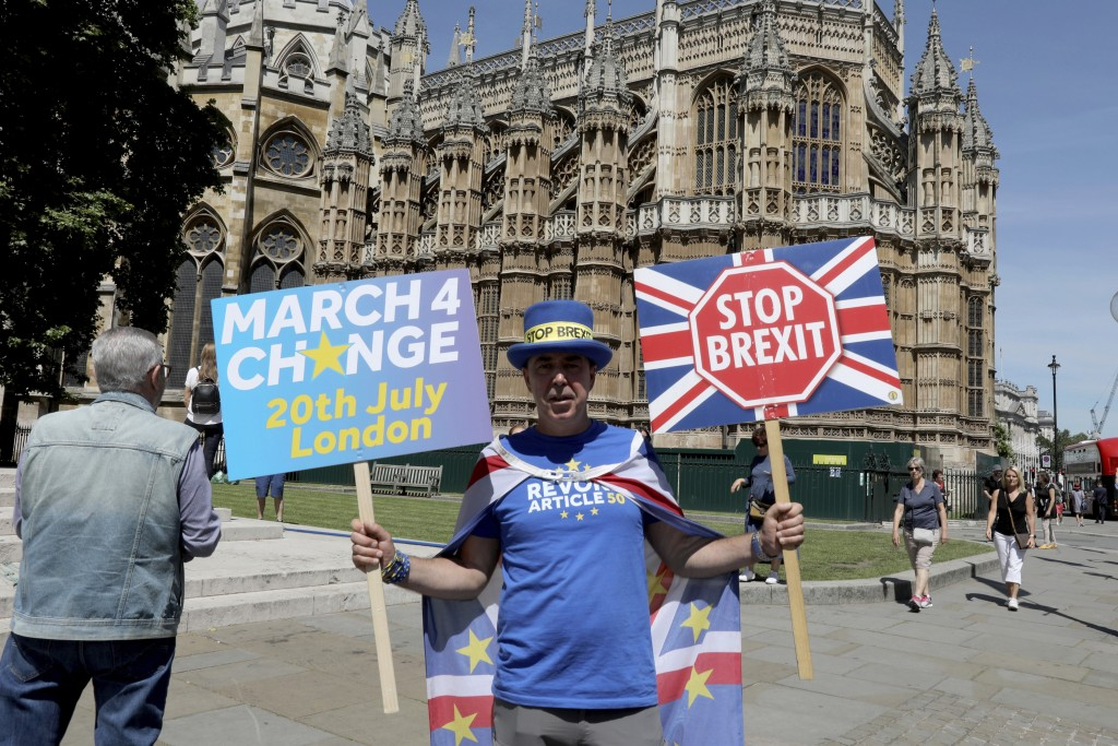 Anti-Brexit protester Steve Bray stand outside Westminster Abbey in London, Thursday, July 4, 2019, as protesters continue to demonstrate various view
