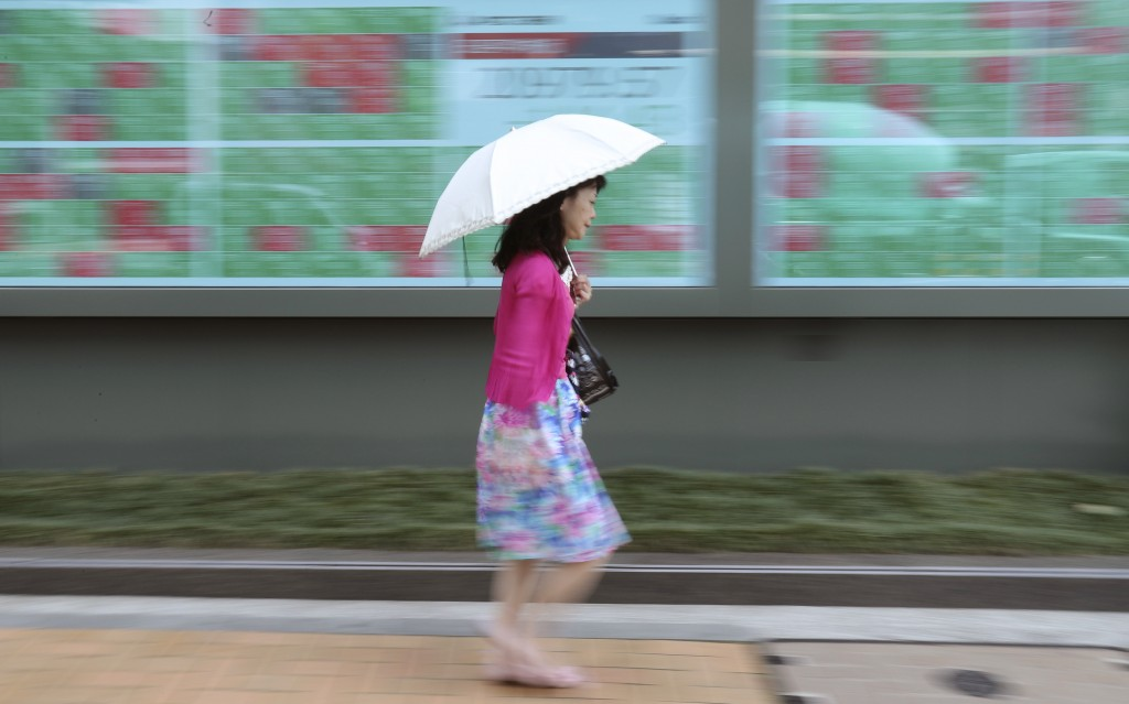In this June 18, 2019, photo, a woman walks by an electronic stock board of a securities firm in Tokyo. Asian stocks fell Friday as investors waited f...