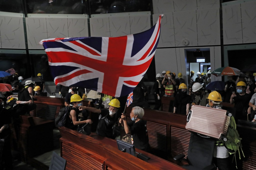 In this Monday, July 1, 2019, photo, Alexandra Wong, 63, carries the British flag as she joins other protesters who stormed the Legislative Council bu...
