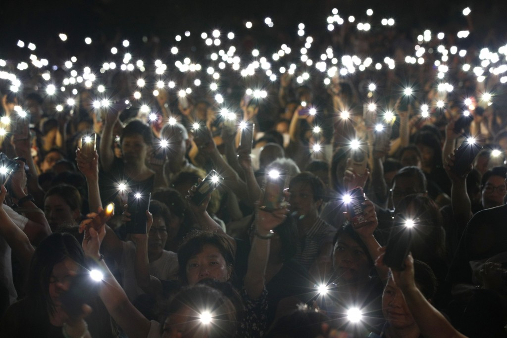 In this Friday, July 5, 2019, file photo, attendees hold up their lit mobile phones during a rally by mothers in support of student protesters in Hong