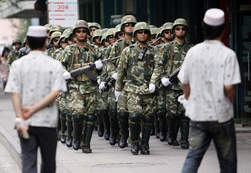 FILE - In this Monday, July 13, 2009, file photo, paramilitary police officers patrol in the aftermath of riots as Uighur men walk by in Urumqi, weste...