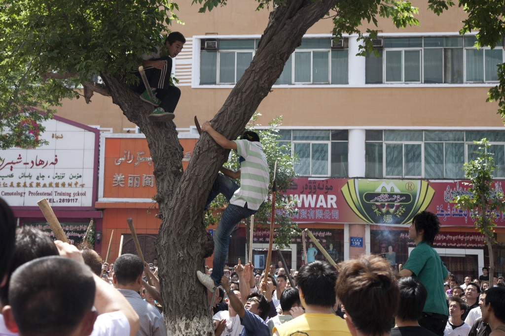 In this photo taken Tuesday, July 7, 2009, armed Han Chinese attempt to attack a suspected Uighur youth stuck in a tree in the aftermath of attacks by