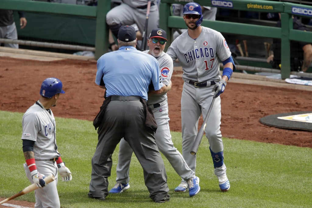 Chicago Cubs manager Joe Maddon, center, yells toward the Pittsburgh Pirates dugout as he is restrained by umpire Joe West and Cubs' Kris Bryant (17)