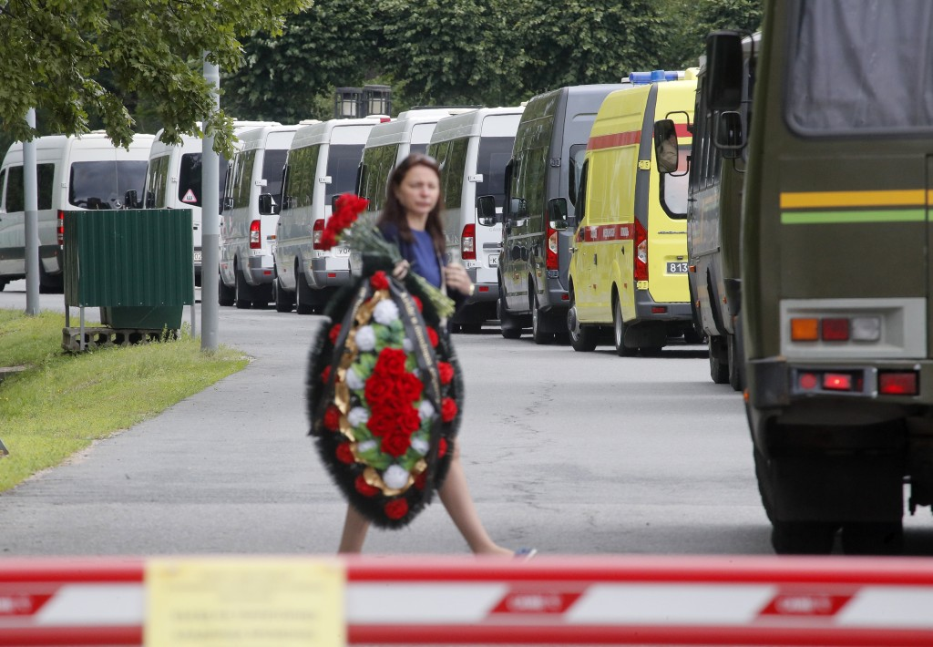 A woman carries a wreath as buses with bodies of the 14 crew members who died in a fire on a Russian navy's deep-sea research submersible, drive to th