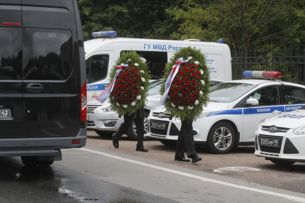 People carry wreaths next to buses with bodies of the 14 crew members who died in a fire on a Russian navy's deep-sea research submersible, waiting to...