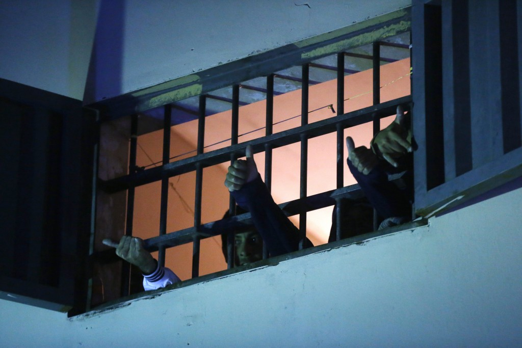 Inmates of La Esperanza prison give the thumbs up to fellow inmate and boxer Richard Moray after his victory against Brazil's Carlos Santos de Jesus i...