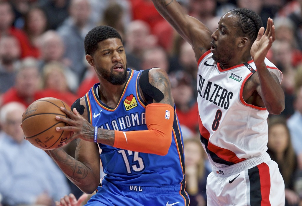 FILE - In this April 16, 2019, file photo, Oklahoma City Thunder forward Paul George, left, looks to pass the ball around Portland Trail Blazers forwa...
