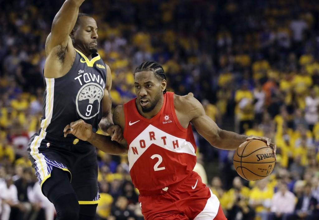 FILE - In this June 13, 2019, file photo, Toronto Raptors forward Kawhi Leonard (2) drives against Golden State Warriors forward Andre Iguodala (9) du