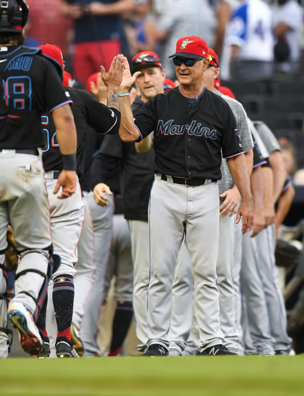 Miami Marlins manager Don Mattingly congratulates players as they come off the field after a baseball game against the Atlanta Braves, Saturday, July ...