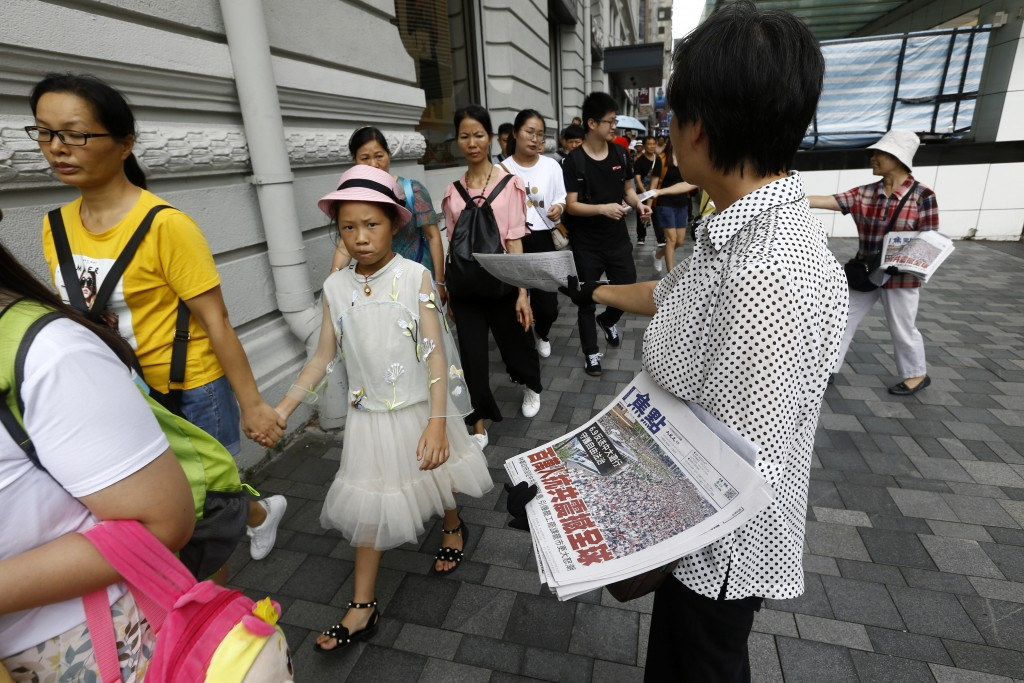 """Hong Kong women distribute newspapers with the headlines """"Millions against Communist China shock the world"""" in a shopping district popular with mainla"""