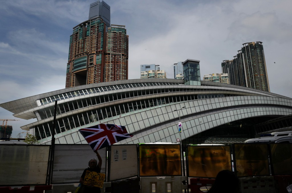 FILE - In this Sept. 22, 2018, file photo, a woman waves a British flag outside the Western Kowloon Station during a protest against the opening cerem