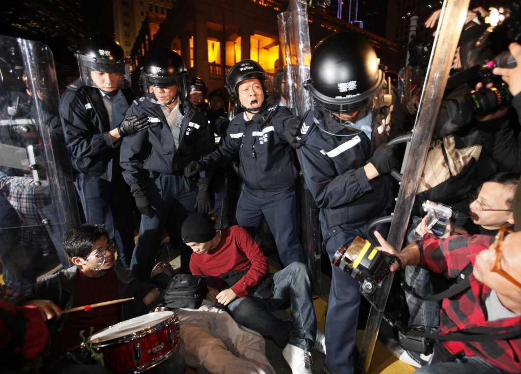 FILE - In this Jan. 16, 2010, file photo, police officers take away the protesters who block a main road during a protest outside Hong Kong's Legislat