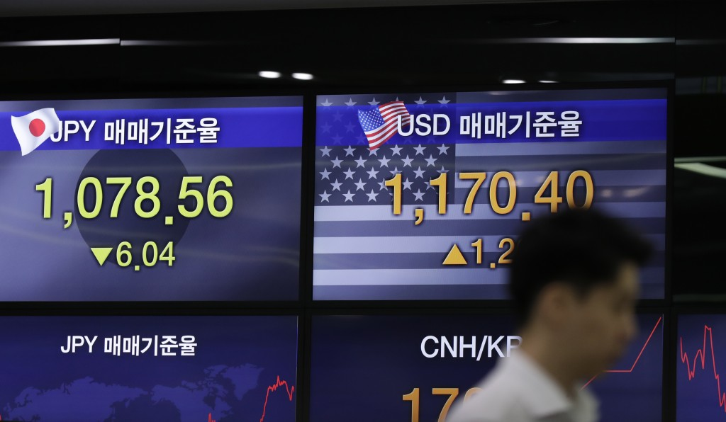 A currency trader stands by the screens showing the foreign exchange rates at the foreign exchange dealing room in Seoul, South Korea, Monday, July 8,...