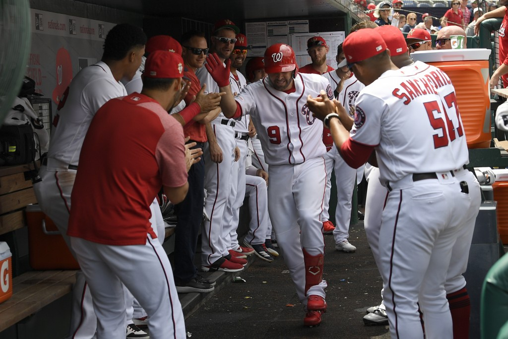 Washington Nationals' Brian Dozier (9) celebrates his home run in the dugout with his teammates during the second inning of a baseball game against th