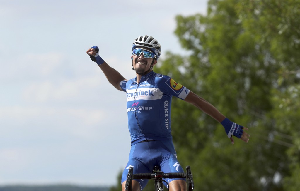 France's Julian Alaphilippe celebrates as he crosses the finish line to win the third stage of the Tour de France cycling race over 215 kilometers (13...
