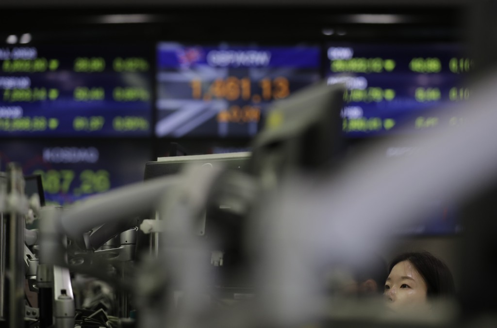 A currency trader watches the computer monitors at the foreign exchange dealing room in Seoul, South Korea, Monday, July 8, 2019. Asian stocks tumbled...