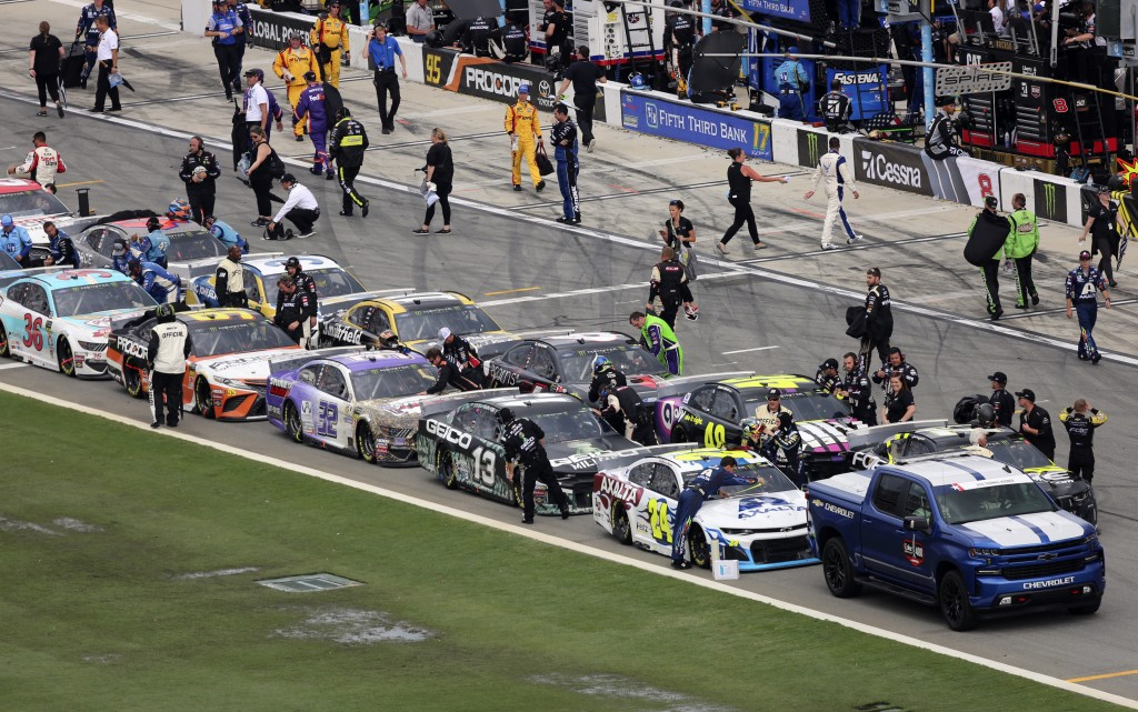 Pit crews begin to cover their cars on pit road as inclement weather moves in causing a delay in the NASCAR Cup Series auto race at Daytona Internatio...