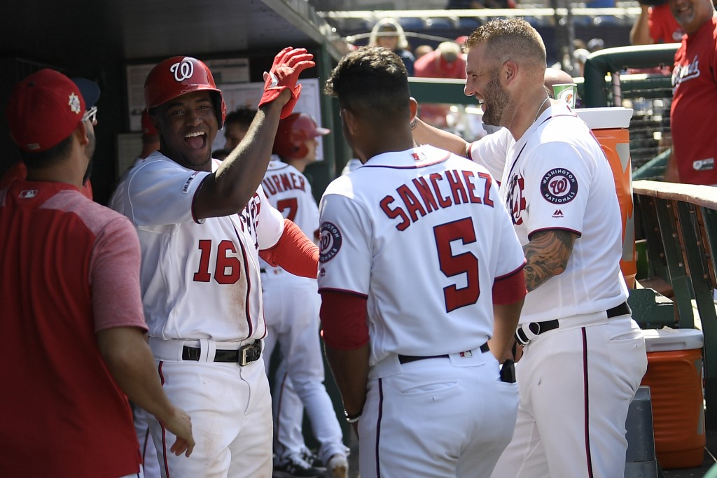 Washington Nationals' Victor Robles, left, celebrates his home run with Adrian Sanchez, center, and Matt Adams, right, in the dugout during the sevent