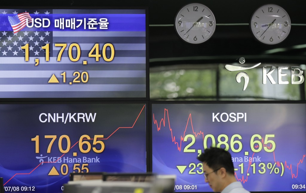 A currency trader walks by the screens showing the Korea Composite Stock Price Index (KOSPI), right, and the foreign exchange rate between U.S. dollar...