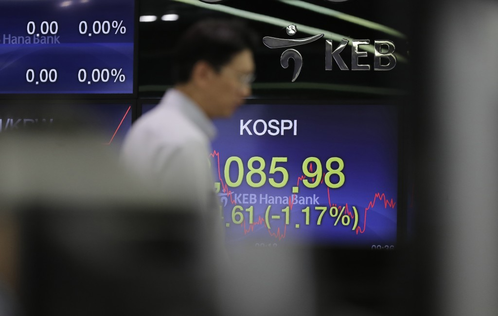 A currency trader talks near by the screen showing the Korea Composite Stock Price Index (KOSPI) at the foreign exchange dealing room in Seoul, South