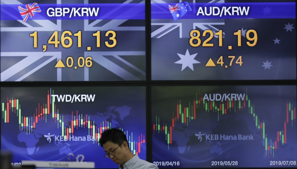 A currency trader walks by the screens showing the foreign exchange rates at the foreign exchange dealing room in Seoul, South Korea, Monday, July 8, ...