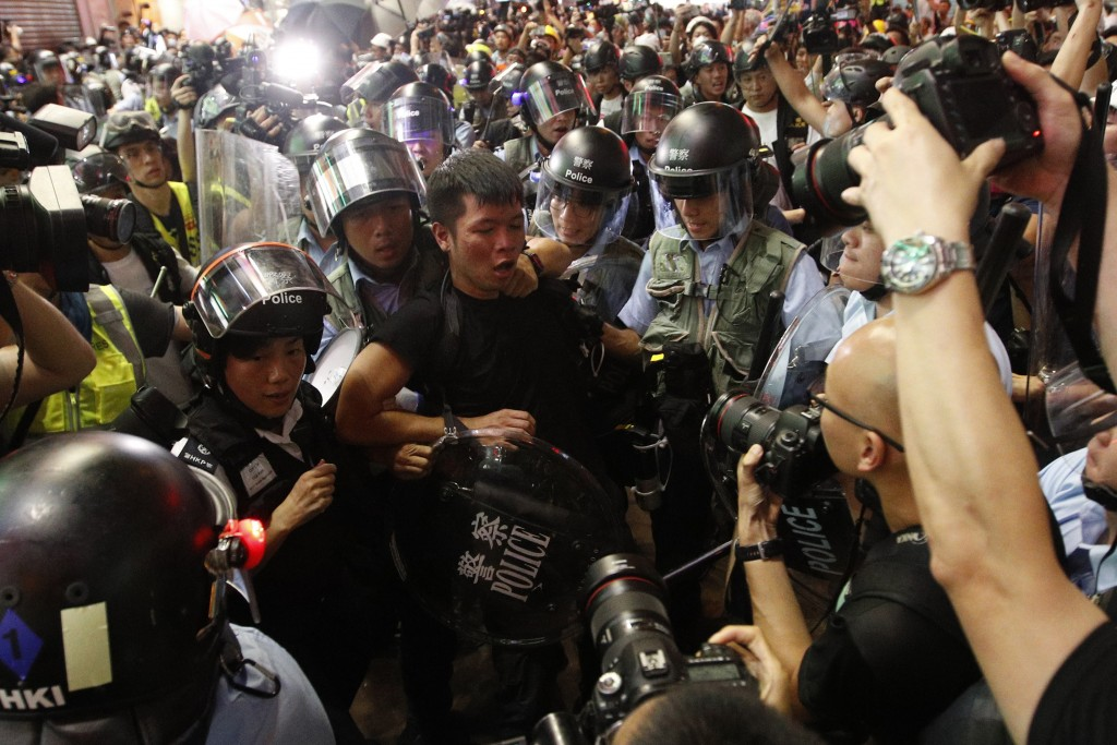 In this Sunday, July 7, 2019, file photo, police officers arrest a protester in Hong Kong. Tens of thousands of people, many wearing black shirts and