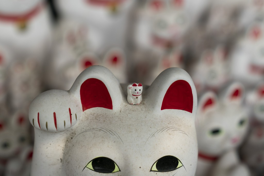 In this June 25, 2019, photo, a small beckoning cat figurine is place on top of a large statue at Gotokuji Temple in Tokyo. According to a centuries-o...